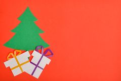 Green Christmas tree with presents. Under red background Stock Photos