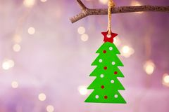 Green Christmas tree with red star ornament hanging on branch. Shining garland golden lights. Purple background. Stock Photo