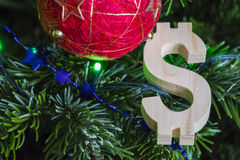 Green Christmas tree with red vintage ball decorations and wooden dollar sign - holiday background royalty free stock photo