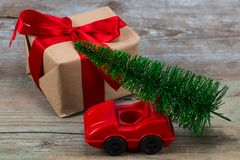 Green Christmas tree on toy car and gift. Christmas holiday celebration concept.  stock photos