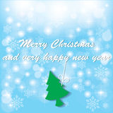 Green Christmas tree was hung on white greeting. Under snowflakes Stock Photos