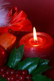 Green christmas wreath decorated with holly,red bu. Rning candle,ribbon royalty free stock image