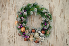 Green Christmas wreath with decorations on wooden background Stock Photos