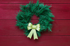 Green Christmas wreath with gold bow hanging on antique red wooden door Royalty Free Stock Photography