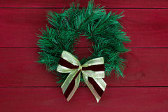 Green Christmas wreath with gold bow hanging on rustic red wooden background Stock Photography