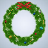 Green Christmas wreath with ornaments and red ribb Royalty Free Stock Photography