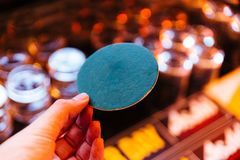 Green circle coaster paper holding with left hand with blur background.  royalty free stock image