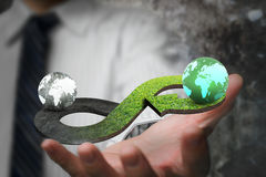 Green circular economy concept. Hand showing arrow infinity symbol with grass texture and two globes of different colors royalty free stock image