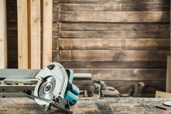 Green circular saw. Modern green circular saw lies on a wooden plank in the workshop royalty free stock image