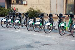 Green city bikes for rent in an urban bicycle rental station. Green city bikes for rent in urban bicycle rental station royalty free stock images