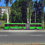 Green city bus stops in city street to take-off the passenger.  Stock Photo