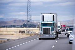 Green classic big rig semi truck reefer unit on traffic road Royalty Free Stock Photos