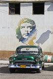 Green Classic Cuban Car and Che painting. Cuba, Havana - 2 January 2011; Green Classic Cuban Car parked in front of Che painting, Havana Stock Image