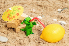 Green clay monster drinking lemon juice Royalty Free Stock Image