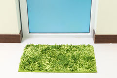 Green cleaning feet doormat or carpet in front of toilet door. Look dirty Royalty Free Stock Image