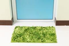 Green cleaning feet doormat or carpet in front of toilet door Royalty Free Stock Image