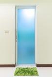 Green cleaning feet doormat or carpet in front of toilet door Stock Photos