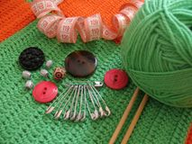 Green clew, buttons and needle for knitting. Green clew, needle  on knitted background Royalty Free Stock Image