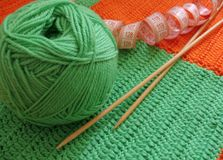 Green clew and needle for knitting. Green clew, needle  on knitted background Royalty Free Stock Photography