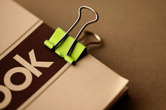 Green clip. Notebook clip on a notebook Royalty Free Stock Photo