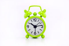Green clock. Small green alarm clock  in white background Royalty Free Stock Images