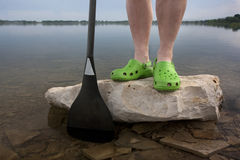 Green clogs and canoe paddle Stock Images