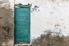 Green closed door on a ruined old white wall royalty free stock images