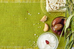 Green cloth background with the space for a text. Traditional Mediterranean motive - feta cheese, tzatziki, olives Royalty Free Stock Photos