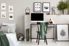 Green cloth on black wooden chair at desk with computer, wooden triangle and cones, real photo with gallery of posters on empty. Grey wall royalty free stock photos