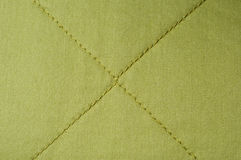 Green cloth with X seam. Close up of green cotton cloth with X seam in the middle Royalty Free Stock Image