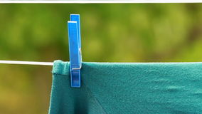 Green clothes hanging to dry on laundry line Stock Photo