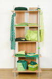 Green clothes nicely arranged on a shelf. Stock Image
