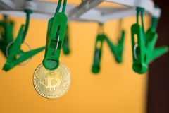 Green clothes peg hold one gold Bitcoin.  Stock Images