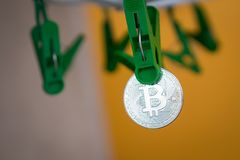 Green clothes peg hold one silver Bitcoin.  Stock Photography