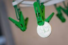 Green clothes peg hold one silver Litecoin.  Stock Photography