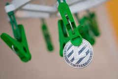 Green clothes peg hold one silver Litecoin.  Royalty Free Stock Photography