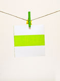 Green clothes-pin holding Greeting card Royalty Free Stock Photography
