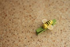 Green clothespeg in the form of a yellow-black bee on a multi-colored red background stock photos