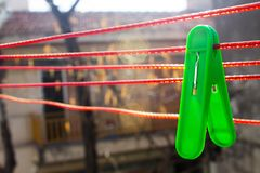 Green clothespin hangs on the red clothesline on the backyard stock photos