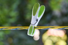 Green clothespin on a rope isolated. Stock Photo