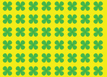 Green Clover. Four leaves green clovers arranged on yellow background Royalty Free Stock Photography