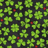 Green clover meadow with ladybirds pattern on dark Royalty Free Stock Photos