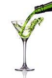 Green cocktail. Splashing into martini glass royalty free stock photography