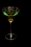 Green cocktail with cherry. Green cocktail with a cherry on black background and glass surface Royalty Free Stock Photo