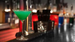 Green cocktail in a glass on the bar. Green cocktail in a glass on a bar counter of wood on a bar background Royalty Free Stock Image