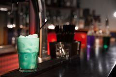 Green cocktail with ice on the bar. Green cocktail with ice on a bar counter of wood on the background of the bar Stock Image