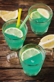 Green cocktail with lemon and ice on the wooden table Stock Images