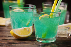 Green cocktail with lemon and ice on the wooden table Royalty Free Stock Photography