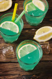 Green cocktail with lemon and ice on the wooden table Stock Image
