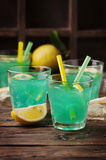 Green cocktail with lemon and ice on the wooden table Royalty Free Stock Image
